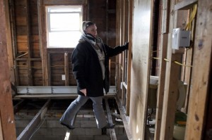 Superstorm Sandy victim Stacey Walsh crosses the floor boards in her decimated home. (Samira Bouaou/All Rights Reserved)